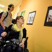 Besucherin im Rollstuhl betrachtet ein Foto.