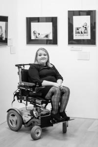 Nastija Fijolic sitzt in ihrem Elektrorollstuhl vor zwei Bildern ihrer Ausstellung.