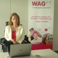 Karin Ofenbeck sitzt vor einem Laptop Hinter ihr ein Plakat mit WAG-Logo und einem Foto auf dem eine lächelnde Frau zu sehen ist, der gerade ein Handtuch über die nassen Haare gewickelt wird.
