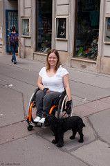 Eeva Airikkala im sitzt Rollstuhl. Sie hält einen Hund an der Leine.