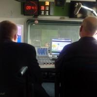 Tonstudio: Zwei Personen sitzen an PCs. Sie sind von hinten zu sehen. Über ihnen eine digitale Zeitanzeige.
