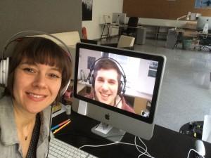 Eine Frau sitzt am PC und schaut in die Kamera. Am Bildschirm ist das Gesicht eines Mannes zu sehen.