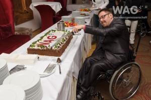 Christoph Dirnbacher schneidet die Geburtstagstorte an. Auf der Torte ist ein WAG-Logo zu sehen.