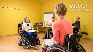 Workshopsituation: Zwei Personen im Rollstuhl sitzen sich gegenüber. Andere Personen beobachten.