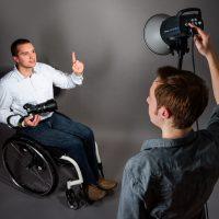 Mann im Rollstuhl hält Kamera in der Hand und zeigt nach oben. Anderer Mann hält Scheinwerfer in der Hand.