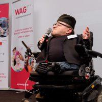 Mann im Rollstuhl mit Hut und Brille. Er macht eine einladende Handbewegung, spricht in ein Mikrophon und ist kleinwüchsig.