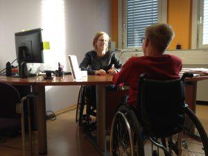 Beratungssituation: Ein Mann und eine Frau im Rollstuhl sitzen sich an einem Schreibtisch gegenüber. Ein Computerbildschirm und Folder sind zu sehen