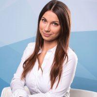 Porträt: Anna Reisinger - Frau mit langem braunen Haar in weißer Bluse