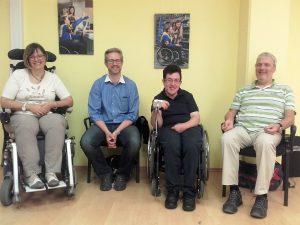 4 Personen sitzen vor einer gelben Wand mit Bildern. 2 davon im Rollstuhl.