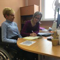 Eine blonde kurzhaarige Frau im Rollstuhl sitzt mit einer langhaarigen Fraun mit Brille an einem Schreibtisch. Die Frau mit Brille schreibt in ein Buch.