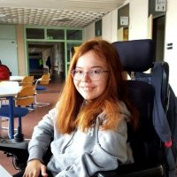 Junge Frau mit langen Haaren und Brille, die in einem Rollstuhl sitzt. Sie lächelt.