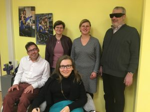 Gruppenfoto, vorne 1 Mann und eine Frau im Rollstuhl. Dahinter stehen 2 Frauen und ein Mann mit schwarzer Brille.