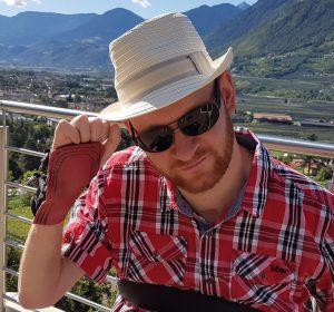 Mann mit Hut und Sonnenbrille. Hinter ihm sind Berge zu sehen.