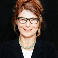 Frau mit Brille und hochgestecktem Haar, die lächelt