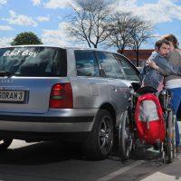 Ein Rollstuhl steht neben einem Auto. Ein Mann stützt sich an einer Person ab. Beide stehen neben der Autotür.