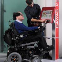 Ein Mann im Rollstuhl steht vor einem Bankomaten. Ein zweiter Mann bedient diesen.