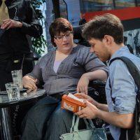 Eine Frau im Rollstuhl und ein Mann sitzen an einem runden Tisch. Der Mann hält eine Geldbörse. Die Frau schaut zur Börse.