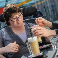 Lachende Frau vor 2 Kaffee-Gläsern. Zwei Hände halten ihr das Glas mit Strohhalm hin.