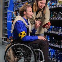Drogerie: Eine Frau hält einem Mann im Rollstuhl mit Blindenschleifeein Parfum hin. Sie scheint ihm etwas zu erklären.