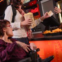 Kino: Frau im Rollstuhl steht beim Popcorn. Stehende Frau hält Popcorn und Gelschein (zum Bezahlen) in der Hand.