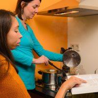 Sitzende Frau liest mit Finger an der Zeile aus einem Kochbuch vor. Stehende Frau kocht.