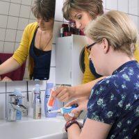 Eine Frau gibt Zahnpaste auf eine Zahnbürste. Die andere Frau hält die Zahnbürste.