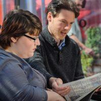 Zwei Personen mit einer Zeitung. Ein junger Mann hält diese. beide scheinen zu lesen.