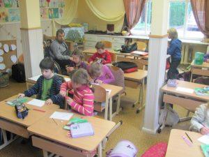 Erwin Buchberger bei der Arbeit mit SchülerInnen. Kinder sitzen an Schultischen und arbeiten. Rollstuhlfahrer sitzt bei ihnen.