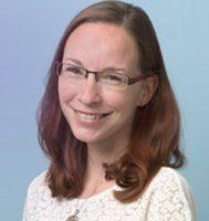 Lächelnde Frau mit Brille und langen braunen Haaren