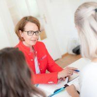 Frau mit mittellangen Haaren und Brille sitzt an einem Schreibtisch. 2 andere Frauen sind von hinten zu sehen. Die Frau trägt eine Rote Jacke.