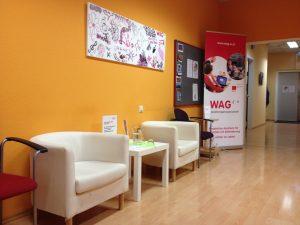 WAG Wartebereich: 2 leere gemütliche Stühle und im Hintergrund ein Rullup mit WAG-Logo