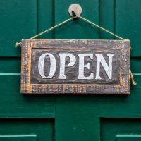 """Türschild mit Schriftzug """"open"""" auf Holz."""